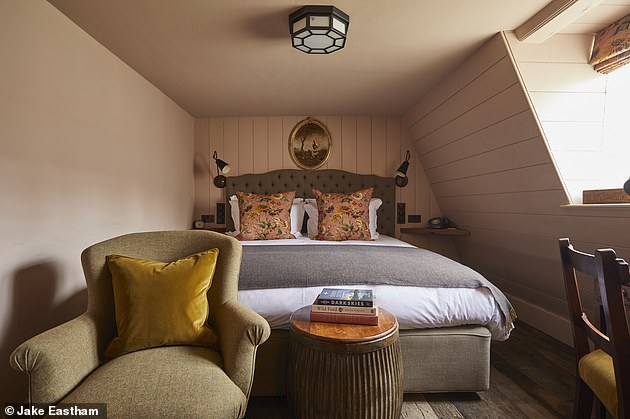 This bedroom has wood panelling on the walls and an armchair for cosying up with a book