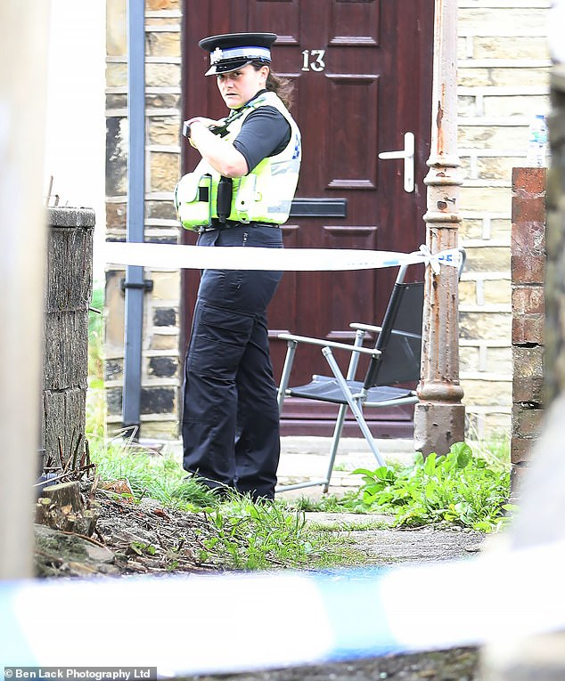 Pictured: A police officer stands guard at the entrance to an alleyway where an 18-year-old girl was raped on Friday