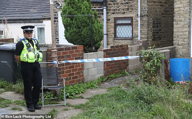 Pictured: A police officer stands guard next to the entrance to the alleyway in which an 18-year-old girl was raped on Friday in broad daylight. Investigations are on-going