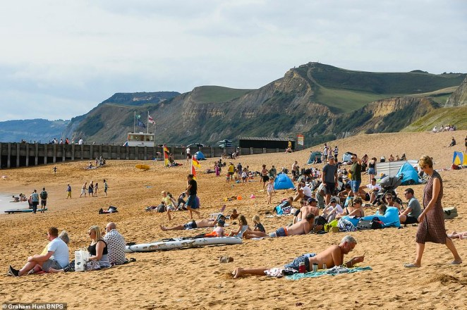 Britain will be hotter than Portugal as Hurricane Larry catapults a 600-mile wide 77F 'subtropical sizzle' to our shores - bringing a second autumn heatwave (pictured: A beach in Dorset today)