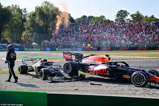 Hamilton (left) walks away from the scene of the crash as stunned spectators in the grandstand absorb what happened