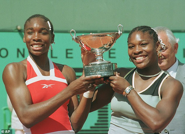 Venus Williams, left, and her sister Serena Williams of the U.S. pose with the trophy after they defeated Martina Hingis of Switzerland and Anna Kournikova of Russia