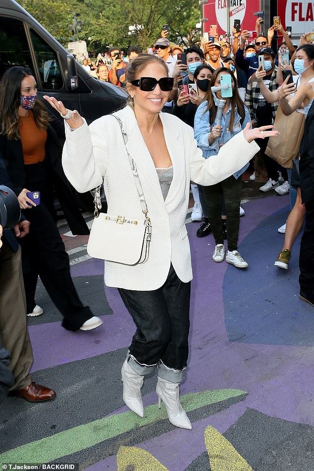 Stylish:The beauty donned a baggy white coat over a grey top with dark denim jeans and heeled boots as she smiled for a sea of adoring fans snapping pics of the star in Union Square