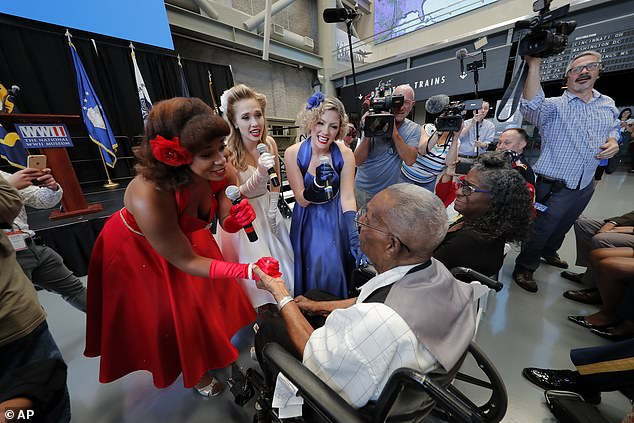 The Victory Belles hold the hands of World War II veteran Lawrence Brooks as they sing him happy birthday celebrating his 110th birthday at the National World War II Museum in New Orleans in 2019
