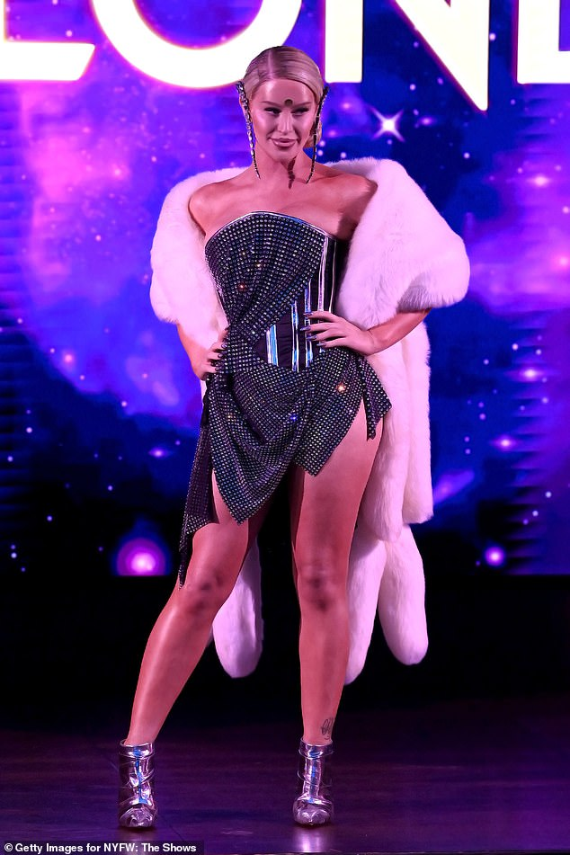 Working the crowd: Gigi on the other hand wore a gunmetal strapless dress with an armored corset with a white fur wrap around her shoulders