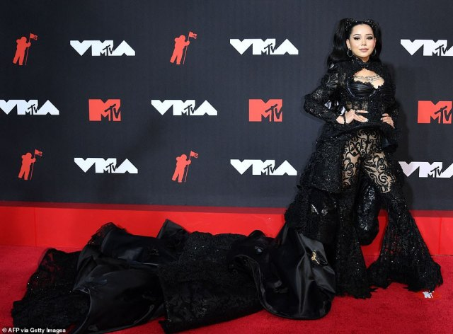Dark angel: Bella Poarch looked like a vampire queen as she stormed the red carpet wearing an intricately beaded bustier with matching bell bottom trousers and a Victorian-inspired cape with tiers of silk following behind her