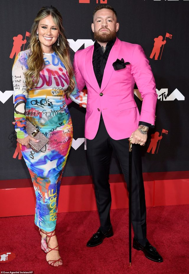 Fighter: Injured MMA fighter Conor McGregor packed some punch in a hot pink jacket with a black tuxedo shirt and a dignified looking cane while there with partner Dee Devlin