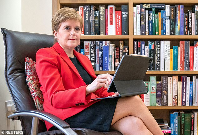 Nicola Sturgeon (pictured writing her conference speech) will today demand Boris Johnson 'cooperates' in holding another independence referendum - despite polls suggesting most Scots don't want one any time soon