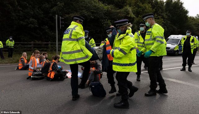 Police officers remove a protester who stopped traffic at junction three of the M25 at Swanley in Kent this morning