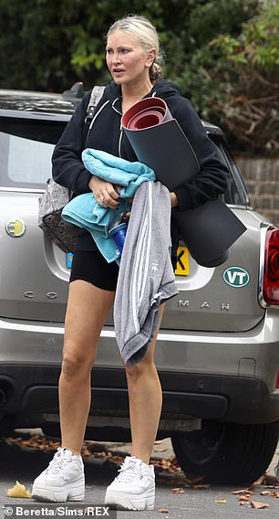 Fully loaded: She bundled her pilates mat, towel, water bottle and grey joggers up in her arms