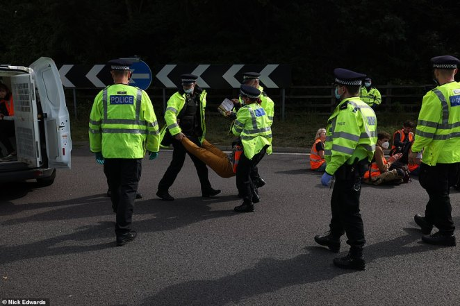 Protesters are taken away by police after the Insulate Britain group caused chaos at the M25 in Swanley, Kent, yesterday
