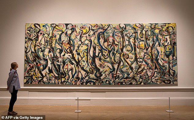 A gallery assistant poses in front of a painting titled 'Mural, 1943' by Jackson Pollock at the Royal Academy of Arts in London on September 20, 2016