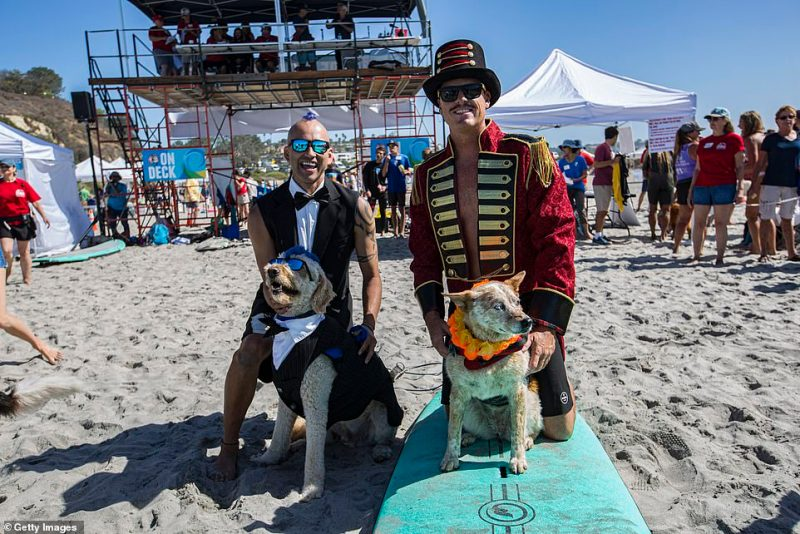 Kioni Russell Gallahue and his surfing partner Derby (L) and Homer Henard with his surfing partner Skyler (R) pose for a photo at Del Mar Dog Beach