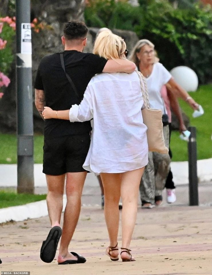 Stroll:After enjoying drinks together poolside, Emily and her handsome companion enjoyed a stroll arm-in-arm, with the presenter slipping into a chic white shirt