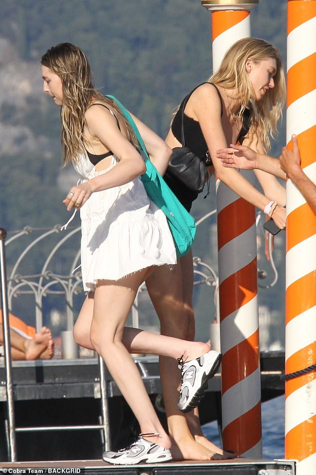 Holiday: The 23-year-old model cut a casual figure for the day as she wore a white mini dress, which she wore over a black bikini top.