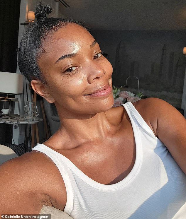 No paint yet: Gabrielle Union looked lovely with no makeup on as she wore a simple white tank top with flowers behind her. She said she was having a 'pre-Met facial'