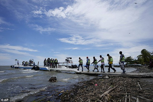 The number of climate migrants may be much higher because the World Bank report does not cover most high-income countries, Middle Eastern countries, small island states, or people migrating to new countries.  Pictured: Haitian refugees walk towards the boats that will take them to Colombia