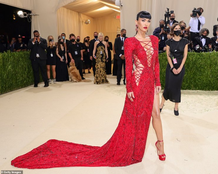 Red hot: Megan wowed in the striking crimson Dundas gown that featured lace up details along the chest and sides; she paired the thigh-revealing number with red heels and a blunt fringe, adding red lipstick