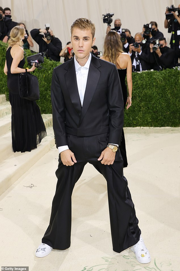 Handsome: While posing for pictures, the Canadian pop star, 27, who wore a dark suit and white button-down, kept one arm tenderly around his spouse's waist