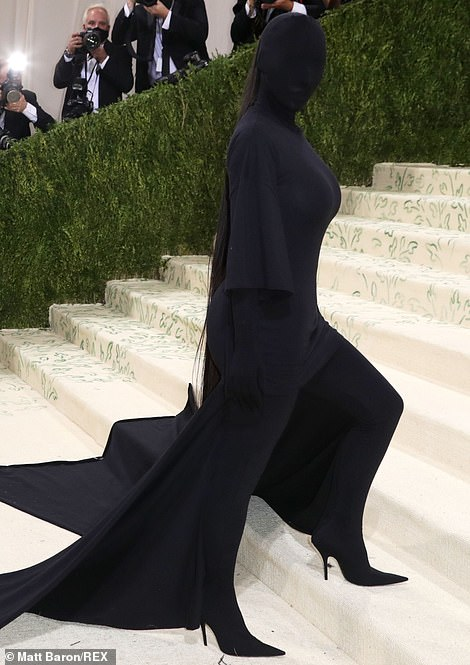 Letting her hair down: Her brunette tresses poked out of the balaclava in the form of a ponytail featuring extensions which hung down to below her derriere