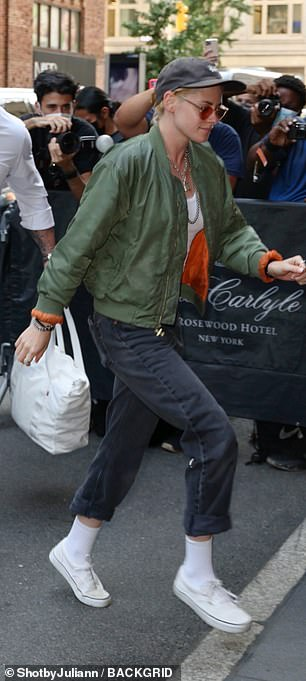 Layers: Her outfit consisted of a green bomber jacket, loose black jeans and a tank top