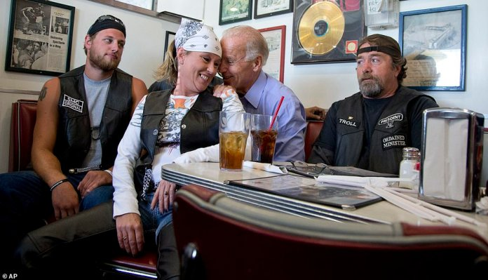 Nuzzling: Biden put his hands on the shoulders of this woman at the Cruisers Diner in Seaman, Ohio, during a September 2012 campaign stop. She had moved his chair in front of the bench where he was sitting between two other bikers
