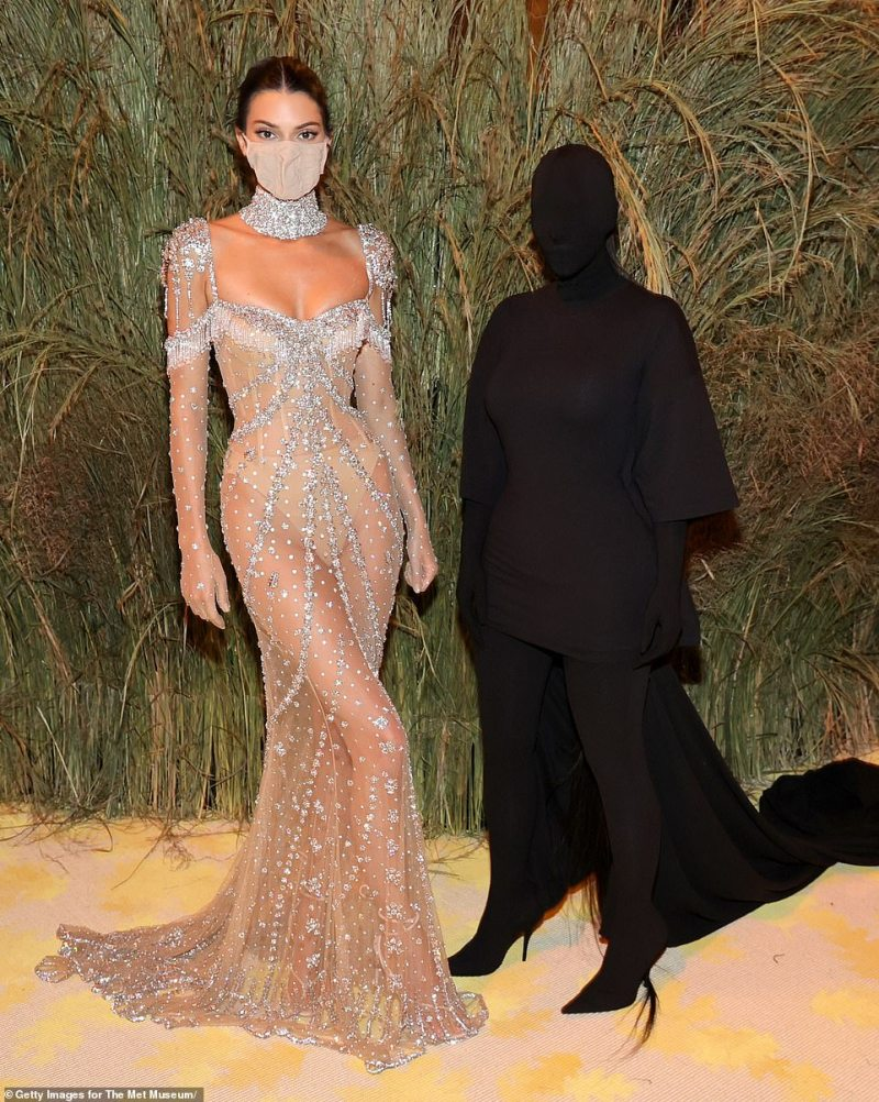 Day and night: She also added a matching mask to take a snap with sister Kim Kardashian, who turned heads in an all-black look that hid her famous face with a mask