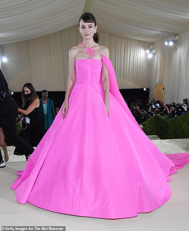 Eye-catching: Carey Mulligan stunned in a vibrant pink bustier gown and matching cape at the Met Gala in New York on Monday night