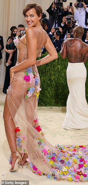Legs for days:The sheer fabric featured a high slit to highlight her toned and tanned legs