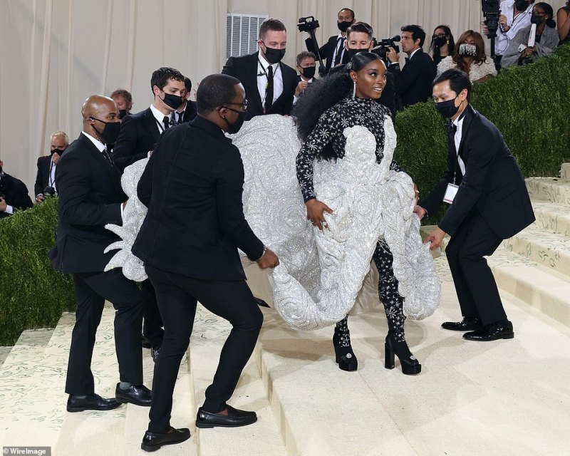 Heavy: Simone enlisted the help of several Gala staff members to help her move up the steps at the Metropolitan Museum of Art