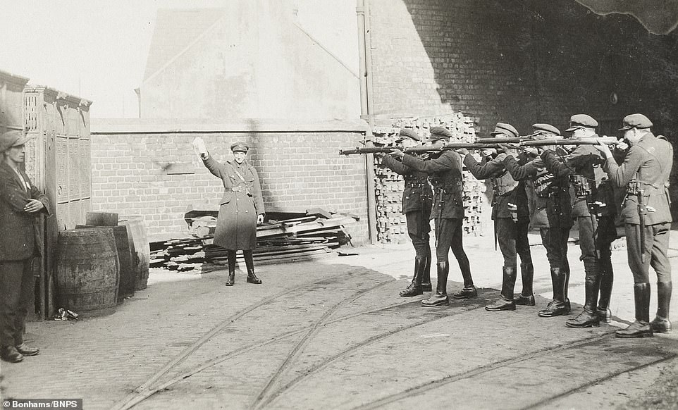 Previously-unseen photographs from a soldier documenting the Irish hostilities of the 1920s have come to light a century later in a fascinating album which includes a chilling image of a man - thought to be an IRA prisoner - standing in front of an firing squad (above). The caption on the execution image simply states: 'Firing squad - execution of a prisoner, Cork 1922'