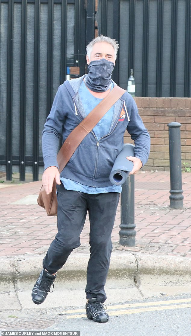 Almost Time: Masked, 55-year-old actor Greg sweats and holds a yoga mat under one arm, holding a big tan on his torso