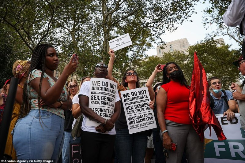 Anti-vaccine protesters held up signs comparing the new mandates with segregation in New York City on Monday