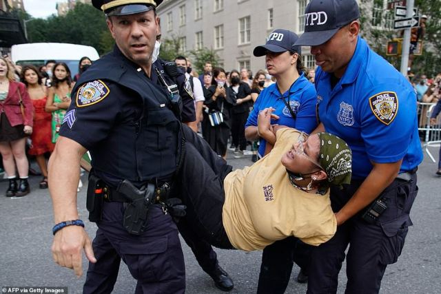A woman gets arrested during a Defund the Police protest outside the Metropolitan Museum of Art during the MET Gala in New York on September 13, 2021 while Rep. AOC and Mayor Bill de Blasio were inside