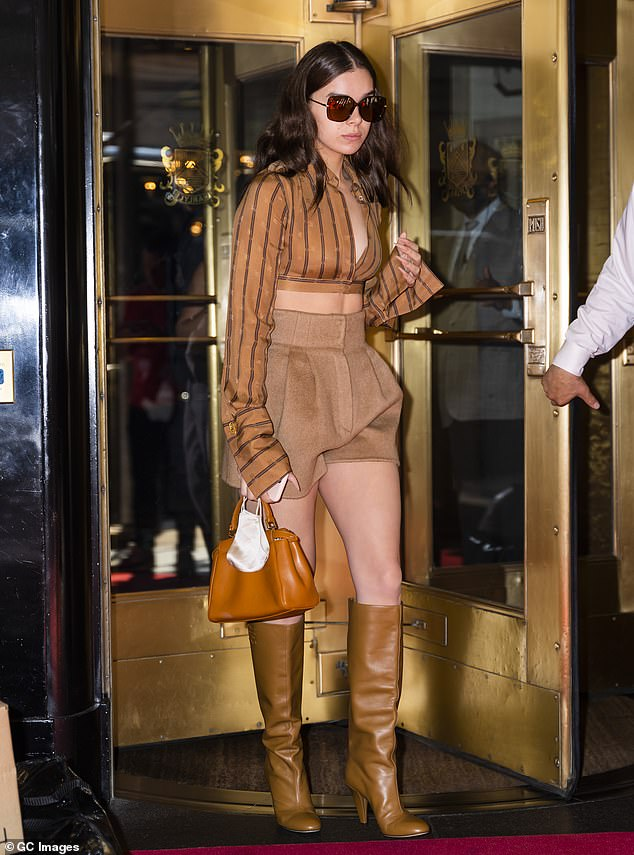 Simply stunning: The 24-year-old starlooked retro chic in her first look as she teamed the low-cut cropped dark orange top with a pair of tiny light brown shorts and knee high leather booties