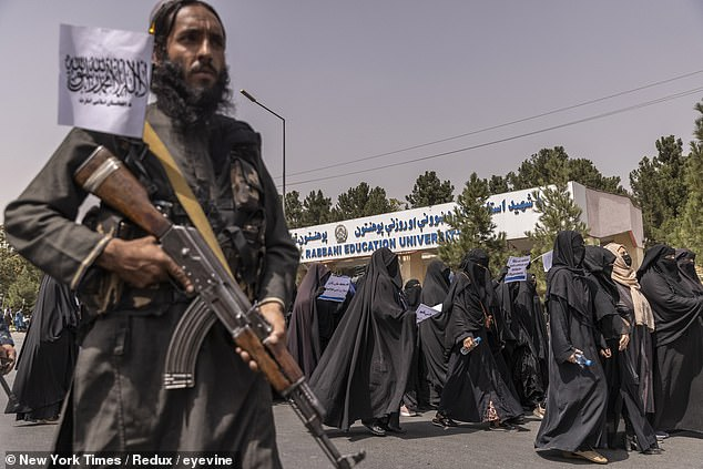 A Taliban fighter stands guard while women, many wearing burqas, march in support of the Taliban in Kabul on Saturday, September 11, 2021