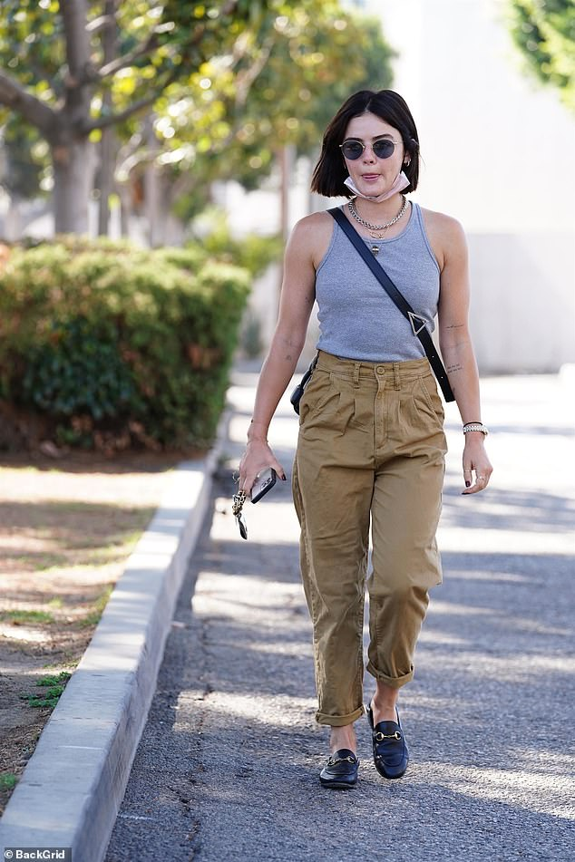 In Details: She accessorized with a pair of designer sunglasses with mirrored lenses and a crossbody bag draped over her shoulder while holding a reusable purple mug