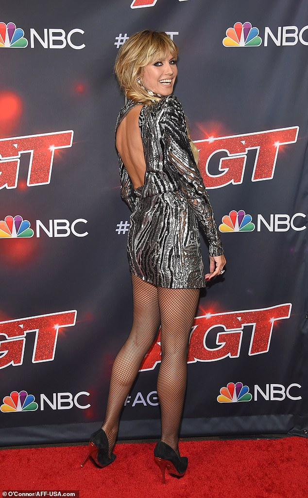 Glitz:Klum put her best foot forward in a glitzy silver zebra print mini dress and a pair of fishnet tights