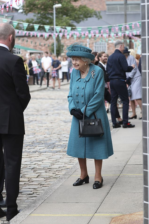 The Queen was surrounded by excited cast members and members of the production team during her visit in July