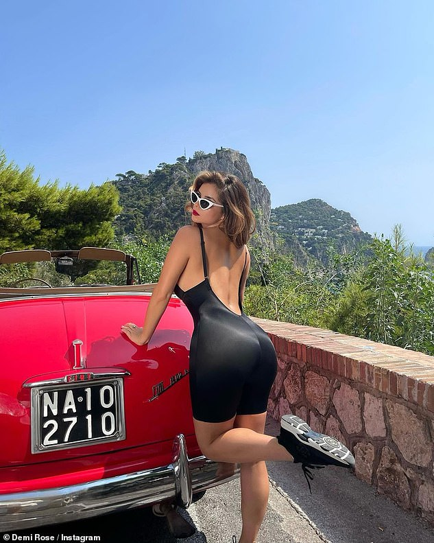 Working it: Demi opted to go braless in the skintight number and appeared in her element as she posed up a storm alongside a vintage car in the scenic countryside