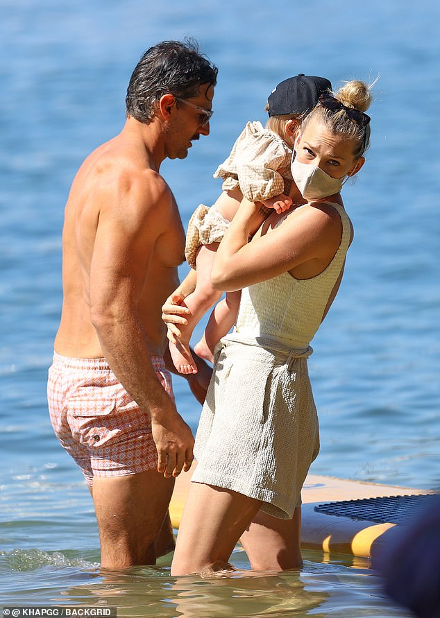 Stars at the beach: The Bachelor couple was spotted in the water next to a floating surfboard as Tim held Elle in one arm before handing her over to Anna, 34