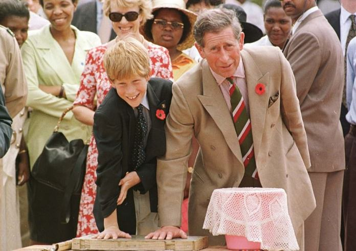 The Prince of Wales is pictured making his mark in cement with Prince Harry at Dookuduku village school in South Africa in 1997