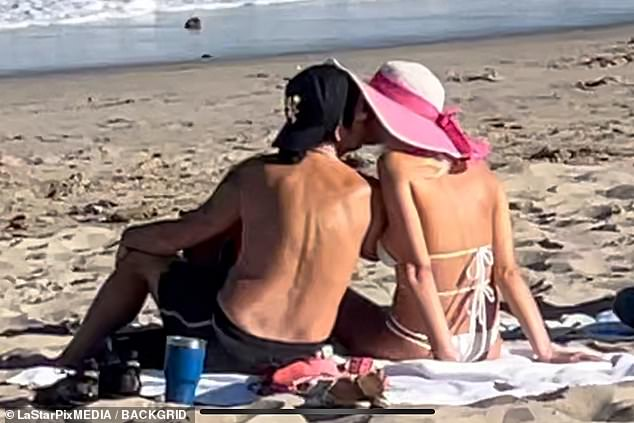 Love: The happy couple took a stroll in Malibu before they shared a sweet kiss as they watched the surf with friends