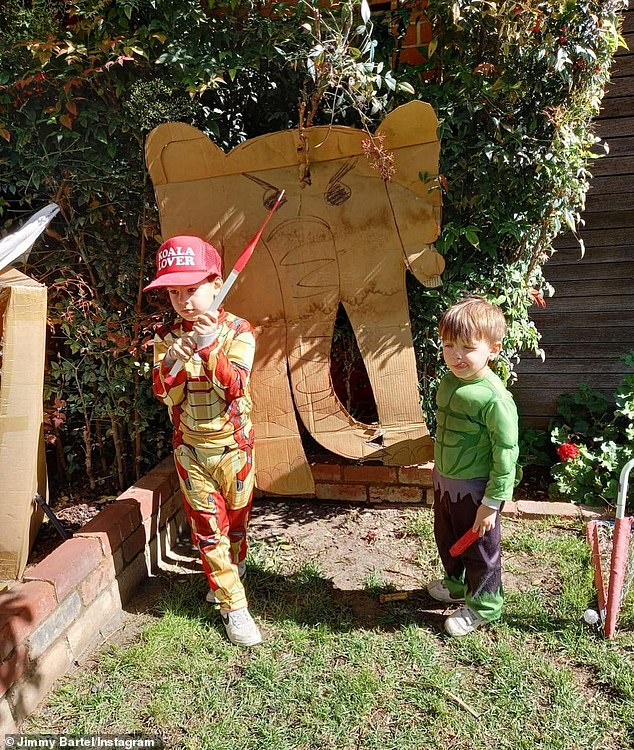 Wild things: Both boys then posed together in front of a cardboard elephant hanging on a tree in Jimmy's backyard
