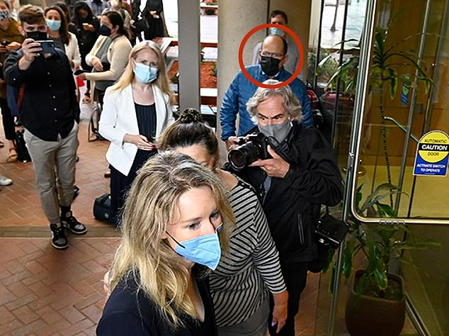Elizabeth Holmes enters theSan Jose federal courtroom on August 31 for day one of jury selection. Among the press was her father-in-law, Bill Evans, in a blue jacket. He wouldn't tell reporters who he was, claiming instead he was a car enthusiast called 'Hanson' who was just a concerned citizen eager to make sure the press was telling the truth. He is shown with DailyMail.com's Chief Investigative Reporter Laura Collins (left) who saw him lining up at 5.30am