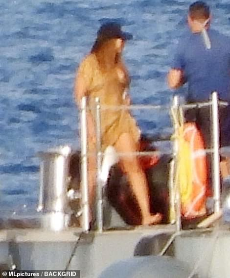 There she is: The R&B legend showed off her curves in a light-colored bikini, worn under a delicate sheer wrap as she cautiously boarded the waiting jet ski