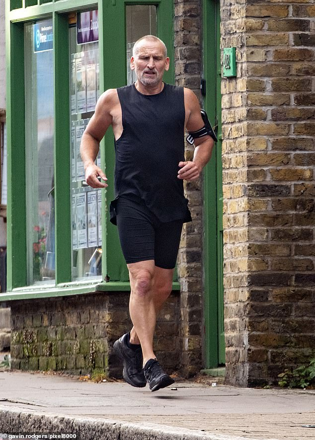 Looking good: Doctor Who star Christopher Eccleston was spotted looking fit and healthy as he displayed his muscular biceps in a black vest on Wednesday