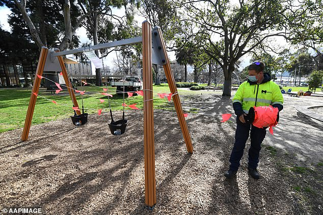 A council worker is seen closing off a swing set at Flagstaff Gardens in Melbourne on August 17 (pictured) after the Andrews Government closed children's playgounds