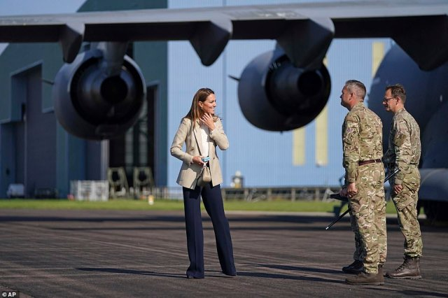 Kate smiles as she speaks to members of the armed forces while visiting RAF Brize Norton in Oxfordshire today