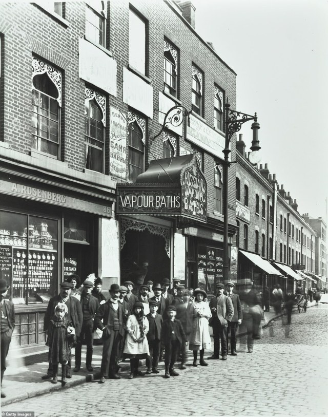 A crowd of men and children are seen looking on as their photo is taken outside the Russian Vapour Baths on Brick Lane in 1904